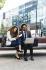 Two smiling young business people with laptop and notebook sitting on bench — Stock Photo