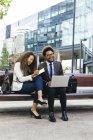 Due giovani uomini d'affari sorridenti con laptop e notebook seduti sulla panchina — Foto stock