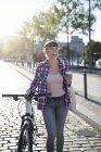 Portrait de jeune femme heureuse avec vélo et café à emporter — Photo de stock