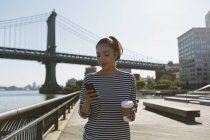 Portrait des USA, New York City, souriante jeune femme avec le café pour aller chercher à son smartphone — Photo de stock