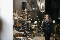 Smiling young woman looking at window display in the evening — Stock Photo