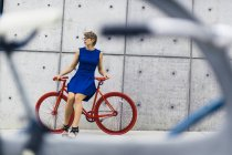Woman with red racing cycle in front of concrete wall — Stock Photo