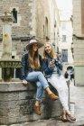 Іспанія, Барселона, двох щасливі молодих жінок, які сидять на фонтан — стокове фото