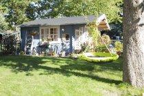 Garten mit Nestschaukel und Gartenhaus — Stockfoto