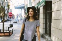 USA, New York City, portrait d'une jeune femme souriante portant un chapeau noir — Photo de stock