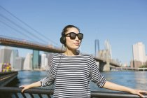 USA, New York City, portrait of  young woman with headphones and sunglasses in front of skyline — Stock Photo