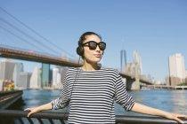 USA, New York City, portrait de jeune femme avec casque et lunettes de soleil en face de la ligne d'horizon — Photo de stock