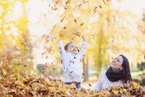 Menina feliz com a mãe brincando com folhas de outono — Fotografia de Stock