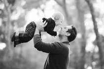Smiling father holding baby boy in the air — Stock Photo