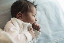 Sleeping newborn baby boy in the cot — Stock Photo