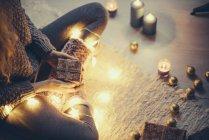Frau sitzt mit Weihnachtsgeschenk und Lichterfee auf dem Teppich — Stockfoto