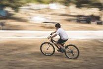 Garotinho pedalando uma bicicleta — Fotografia de Stock