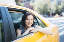 Portrait de USA, New York City, de la souriante jeune femme assise à l'intérieur de la cabine jaune — Photo de stock