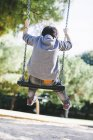 Rear view of boy on a swing at the playground — Stock Photo