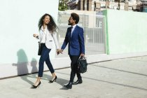 Smiling young couple wearing business clothing walking hand in hand on pavement — Stock Photo