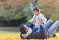 Pai feliz com filha em folhas de outono — Fotografia de Stock