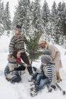 Austria, Altenmarkt-Zauchensee,  happy family with Christmas tree in winter forest — Stock Photo