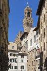 Italien, Florenz, Turm des Palazzo Veccio mit Häuserfassaden im Vordergrund — Stockfoto