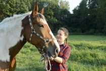 Молодая женщина, стоящая в поле, держа лошадь — стоковое фото