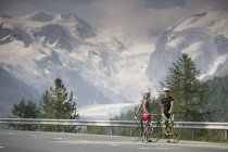Two cyclists on Bernina Pass road in front of Morteratsch Glacier — Stock Photo