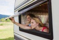Две подруги, глядя через окно караван — стоковое фото
