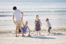 Four siblings playing on the beach together — Stock Photo