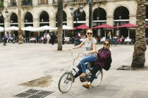 Two happy young women sharing bicycle in the city — Stock Photo