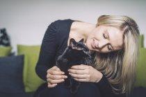 Блондинка и её чёрная кошка на диване — стоковое фото
