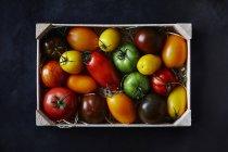 Bunte Tomaten in Holzkiste — Stockfoto