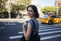 USA, New York City, Manhattan, portrait of smiling young woman crossing a street — Stock Photo