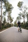 Cyclist with bike standing on road — Stock Photo