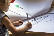 Маленькая девочка рисует и пишет — стоковое фото