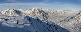 Regno Unito, Scozia, Glencoe, Glen Etive, donna che cammina in montagne innevate — Foto stock