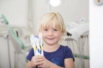 Mädchen in Zahnarztpraxis hält Zahnbürsten — Stockfoto