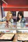 Zwei junge Frauen, die Wahl Pizza zum mitnehmen — Stockfoto
