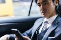 Homme d'affaires souriant sur la banquette arrière de la voiture à l'aide de téléphone portable — Photo de stock