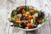 Salada mista fresca em tigela sobre fundo de madeira — Fotografia de Stock