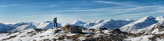 UK, Scotland, Glencoe, Glen Etive, woman hiking in snow-covered mountains — Stock Photo