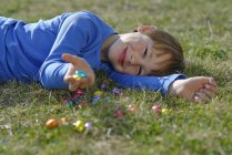 Smiling boy lying on a meadow with many chocolate eggs — Stock Photo