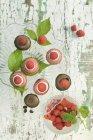 Raspberry macarons and chocolate macarons garnished with raspberries on a cake stand — Stock Photo