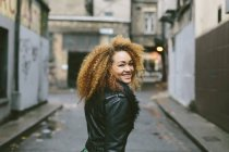 Lächelnde Frau mit Afro-Haaren, die über ihre Schulter schaut — Stockfoto