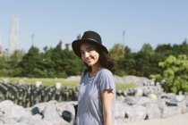 Portrait of smiling young woman wearing black hat — Stock Photo