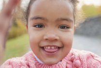 Portrait of smiling mixed race girl sticking out tongue — Stock Photo