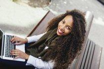 Mulher jovem sorridente usando laptop no banco — Fotografia de Stock
