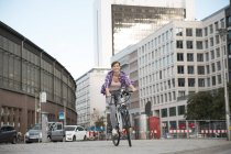 Germany, Berlin, young woman riding bicycle — Stock Photo