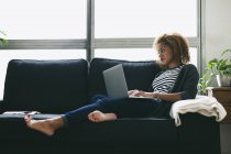 Woman using laptop on couch — Stock Photo