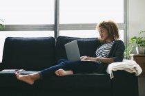 Femme à l'aide de portable sur canapé — Photo de stock