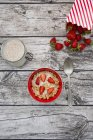Granola with popped amaranth and strawberries in bowl on grey wood with ingredients — Stock Photo