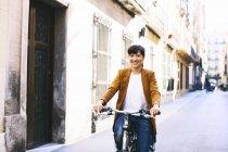 Femme souriante avec vélo dans la ville — Photo de stock