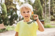 Portrait of blond little boy holding sunglasses — Stock Photo